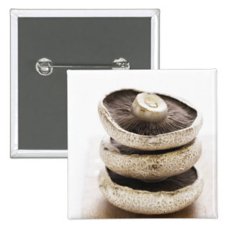 Three flat mushrooms in pile on wooden board button