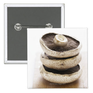 Three flat mushrooms in pile on wooden board, button