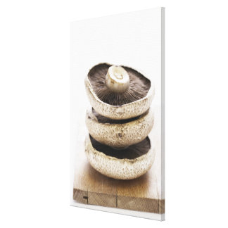 Three flat mushrooms in pile on wooden board, canvas print