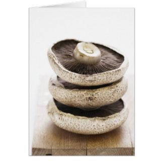 Three flat mushrooms in pile on wooden board, card
