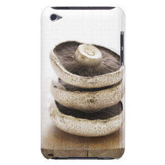 Three flat mushrooms in pile on wooden board iPod touch cover