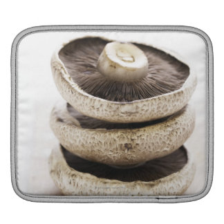 Three flat mushrooms in pile on wooden board sleeve for iPads