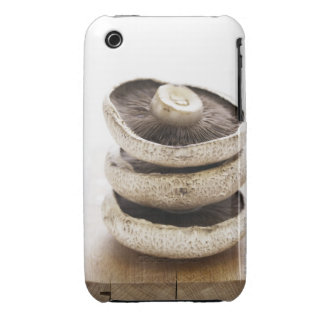 Three flat mushrooms in pile on wooden board, iPhone 3 cover