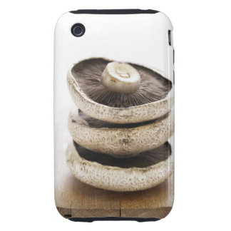 Three flat mushrooms in pile on wooden board, iPhone 3 tough cover