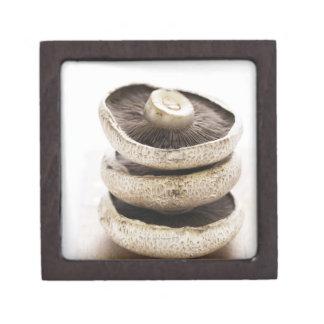 Three flat mushrooms in pile on wooden board, jewelry box