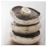 Three flat mushrooms in pile on wooden board, large square tile