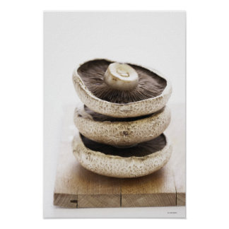 Three flat mushrooms in pile on wooden board poster