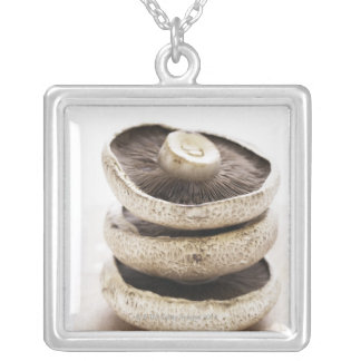 Three flat mushrooms in pile on wooden board silver plated necklace