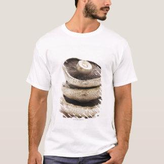 Three flat mushrooms in pile on wooden board T-Shirt