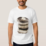 Three flat mushrooms in pile on wooden board, tee shirts