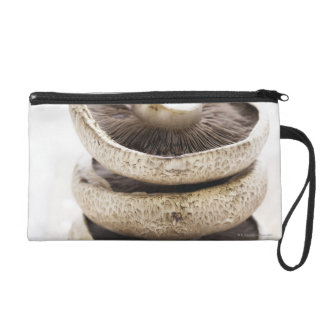 Three flat mushrooms in pile on wooden board wristlet
