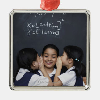 Three girls in classroom whispering metal ornament