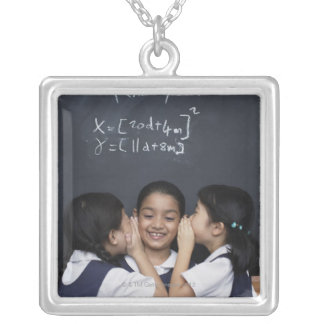 Three girls in classroom whispering silver plated necklace