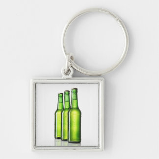 Three green bottles of beer on white background, keychain