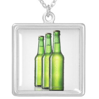 Three green bottles of beer on white background, square pendant necklace