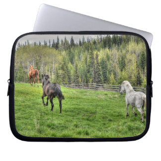 Three Horses Running on Fresh Grass in a Paddock Laptop Sleeve
