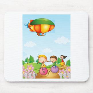 Three kids playing below an airship mouse pad