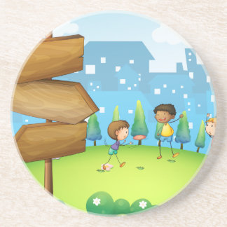 Three kids playing in the hill with wooden arrowbo beverage coaster