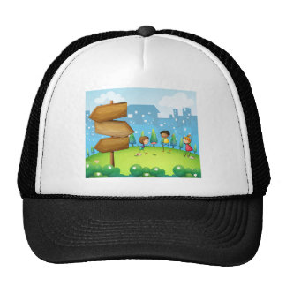 Three kids playing in the hill with wooden arrowbo trucker hat