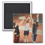 three men in athletic clothing playing refrigerator magnets