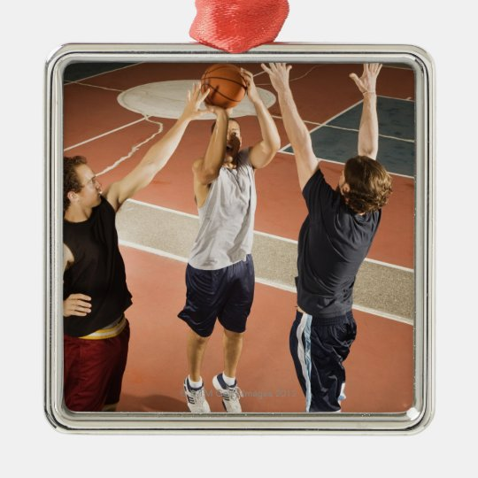 three men in athletic clothing playing metal ornament