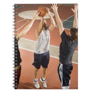 three men in athletic clothing playing notebook