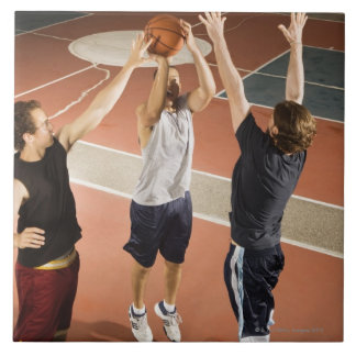 three men in athletic clothing playing tile