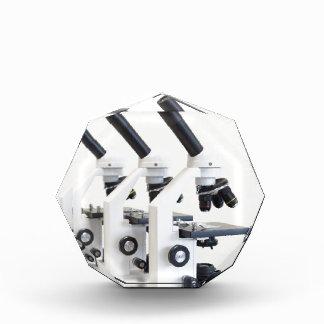 Three microscopes in a row isolated on background acrylic award