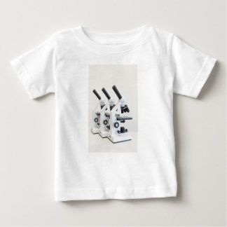 Three microscopes in a row isolated on background baby T-Shirt