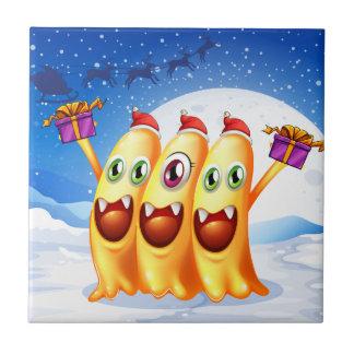 Three monsters celebrating christmas ceramic tile
