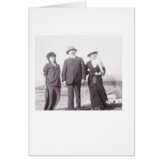 Three people at a beach card