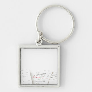 Three receipts on white background. There are Silver-Colored Square Keychain