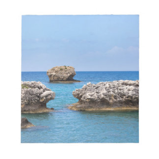 Three separate rocks offshore in sea notepad
