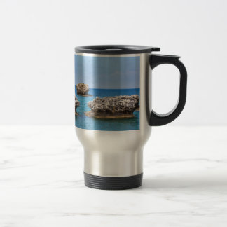 Three separate rocks offshore in sea travel mug