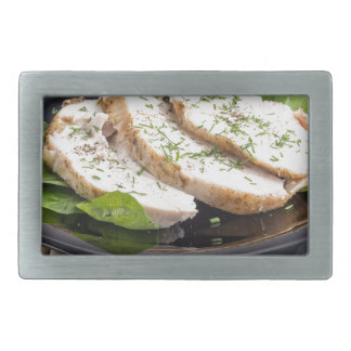 Three slices of roasted chicken on a black plate belt buckle