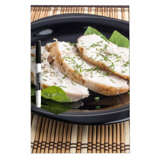 Three slices of roasted chicken on a black plate dry erase board