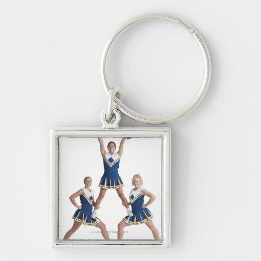 three teenage caucasian female cheerleaders in key chains