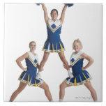 three teenage caucasian female cheerleaders in tile