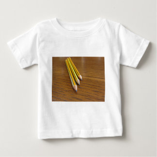 Three used pencils on wooden table baby T-Shirt