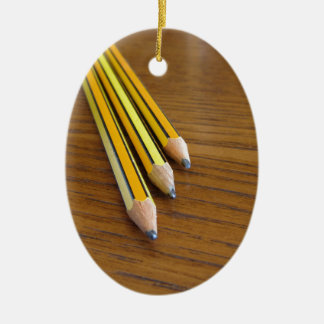 Three used pencils on wooden table ceramic ornament