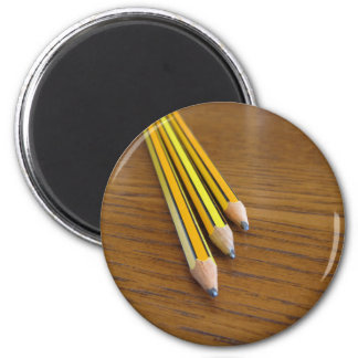 Three used pencils on wooden table magnet