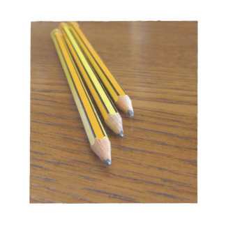 Three used pencils on wooden table notepad
