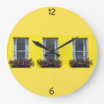 Three windows on a yellow wall clock