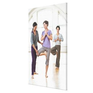 Three women practicing yoga canvas print