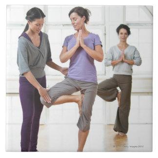 Three women practicing yoga large square tile