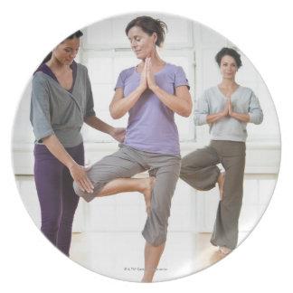 Three women practicing yoga plate