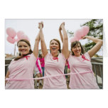 Three young women dressed in pink run in card