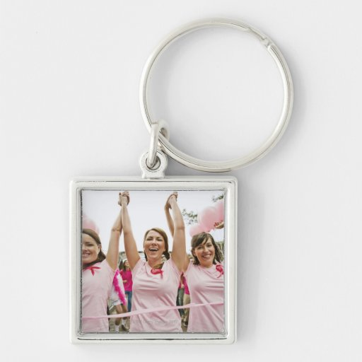 Three young women dressed in pink run in keychain