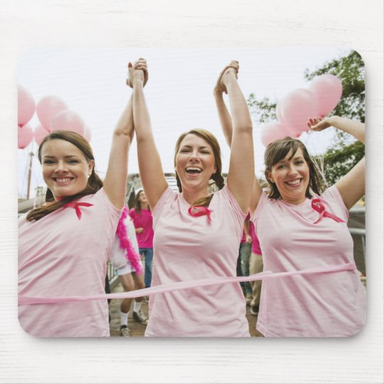 Three young women dressed in pink run in mouse pad