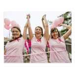 Three young women dressed in pink run in postcards